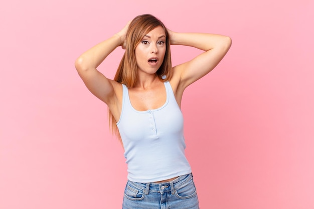 かなり大人の女性が頭に手を置いて、ストレス、不安、または恐怖を感じています