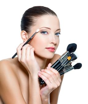 Довольно взрослая женщина, делающая макияж вокруг глаз.