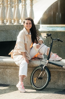 Pretty adult woman posing with eco friendly bike