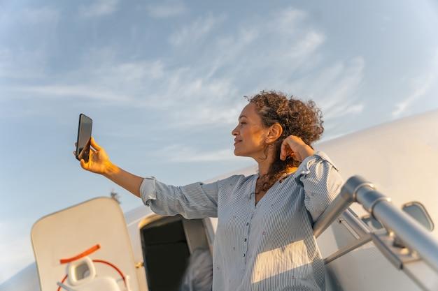 飛行機のはしごの上に立って写真を撮るかなり大人の女性
