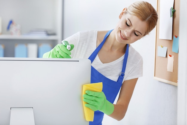 Pretty adult woman wiping computer in office