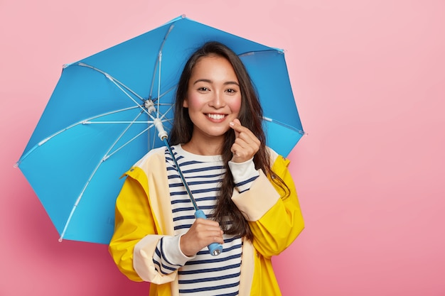 Pretty affectionate asian woman makes korean like sign, has happy expression, gentle smile, stands under umbrella, wears yellow raincoat