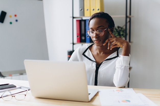 Pretty african american business woman working on laptop in office