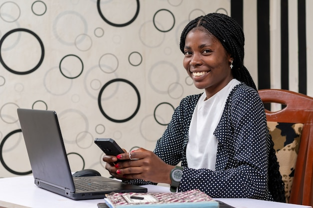 Pretty african american businesswoman smiling while operating her phone in the office