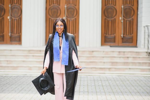 Выпускница довольно афро-американских женщин за пределами здания колледжа