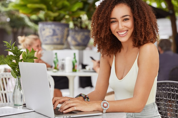 Pretty african american female model keyboards something on laptop computer, connected to free wireless internet in cafe, writes new article for her blog