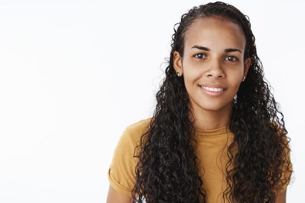 満足のいく笑顔でカメラを見ているかなりアフリカ系アメリカ人の女子学生