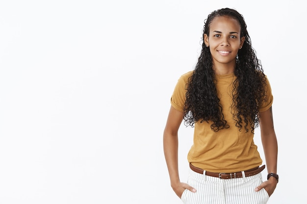 Pretty african american female student looking at camera with pleased smile