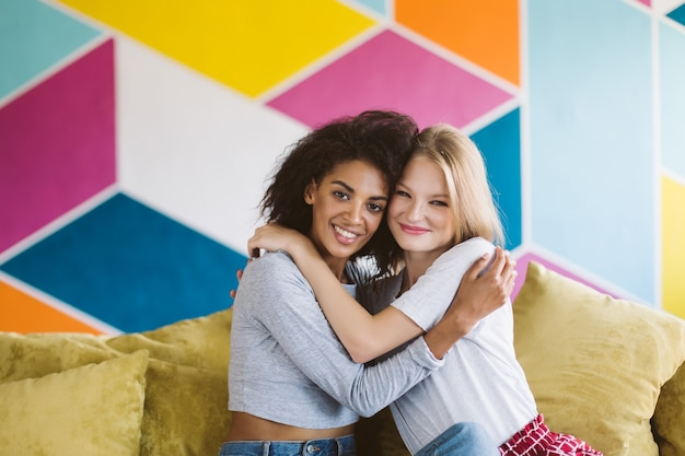 Pretty african american girl with dark curly hair and smiling girl with blond hair happily hugging each other while joyfully  with colorful wall