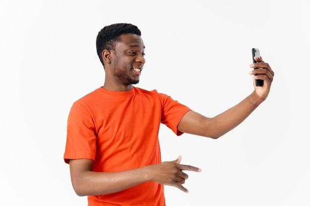 明るい背景のコピースペースに携帯電話でかなりアフリカ系アメリカ人
