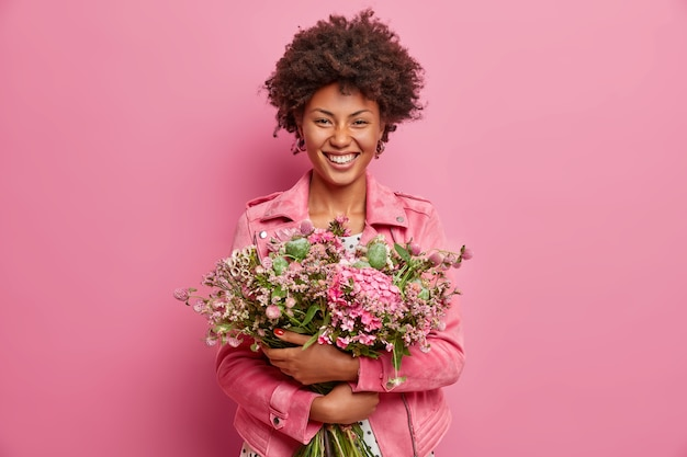 Pretty african american woman expresses sincere emotions, embraces bouquet of flowers, has spring mood