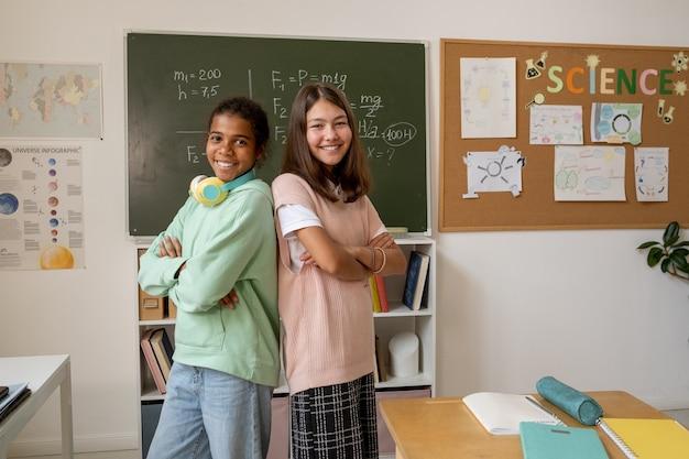 교실에서 카메라 앞에 서 있는 예쁜 아프리카 및 백인 여학생