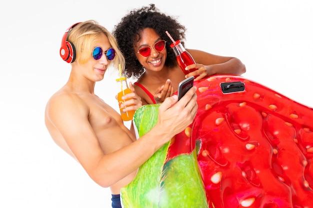Довольно африканская женщина и кавказский белокурый мужчина стоят в купальниках с резиновыми пляжными матрасами, пьют сок и смотрят фотографии на телефон, изолированные на белой стене