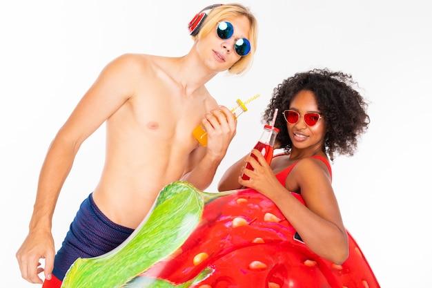 Довольно африканская женщина и кавказский белокурый мужчина стоит в купальнике с резиновыми пляжными матрасами, пьет сок и слушает музыку, изолированную на белой стене