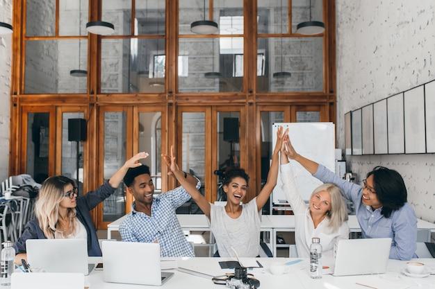 Fotografo femminile abbastanza africano che si diverte con designer e programmatori in ufficio. foto di interni di specialisti freelance che ridono che scherzano nella sala conferenze.
