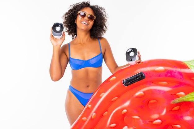 Милая африканская женщина стоит в купальнике с резиновым пляжным клубничным матрасом, слушает музыку и улыбается