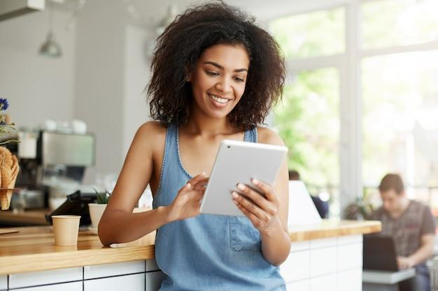 Довольно африканская студентка отдыхая в кафе усмехаясь смотрящ экран таблетки.