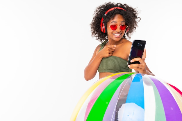 Pretty african female in swimsuit stands with big colourful rubber ball, listen to music with earphones and do selfie isolated