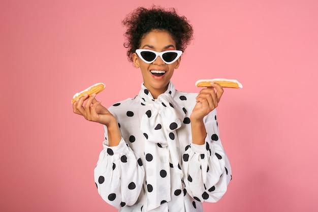 Bella femmina africana con la faccia suprice tenendo i dolci e in posa su sfondo rosa