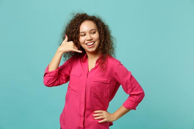 Bella ragazza africana in abiti casual che fa un gesto telefonico come dice di richiamarmi, guardando da parte isolato su sfondo blu turchese. persone sincere emozioni, concetto di stile di vita. mock up copia spazio.