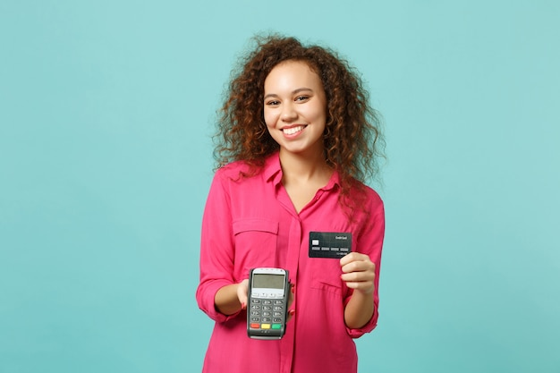 Pretty african girl hold wireless modern bank payment terminal to process, acquire credit card payments isolated on blue turquoise background. people emotions, lifestyle concept. mock up copy space.