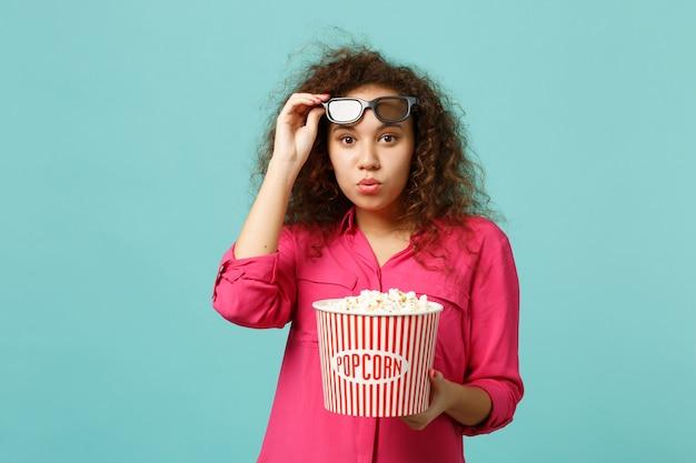 3d 아이맥스 안경을 쓴 예쁜 아프리카 소녀가 영화를 보고 스튜디오의 파란색 청록색 벽 배경에 격리된 팝콘을 들고 있습니다. 영화, 라이프 스타일 개념에서 사람들의 감정. 복사 공간을 비웃습니다.