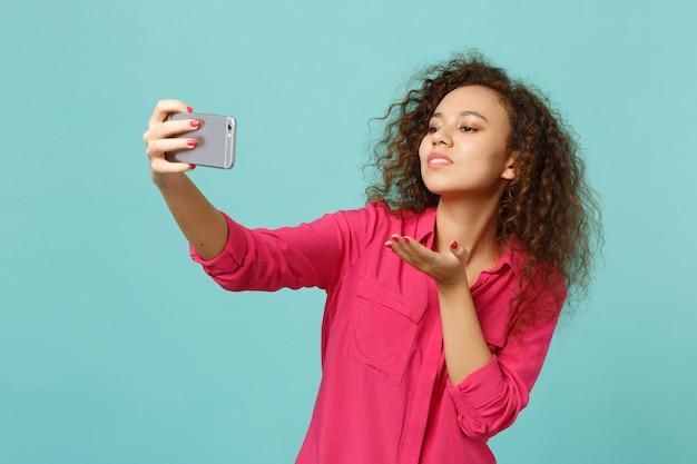 Довольно африканская девушка в повседневной одежде дует, отправляя воздушный поцелуй, делая селфи на мобильном телефоне, изолированном на синем бирюзовом фоне. люди искренние эмоции, концепция образа жизни. копируйте пространство для копирования.