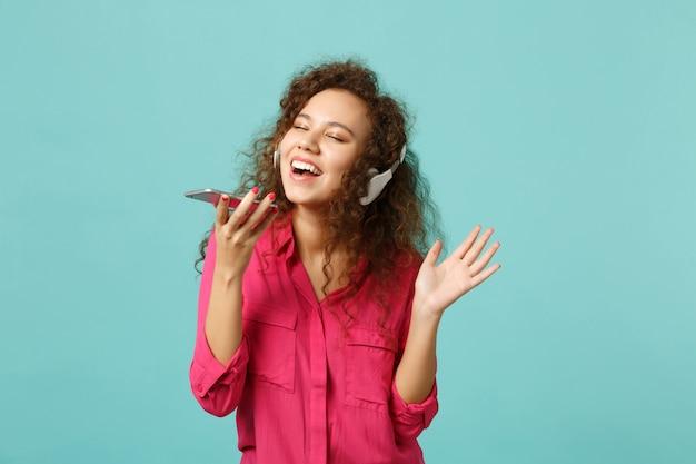 Довольно африканская девушка в повседневной одежде держит мобильный телефон, слушая музыку с наушниками, изолированными на синем бирюзовом фоне в студии. концепция образа жизни искренние эмоции людей. копируйте пространство для копирования.