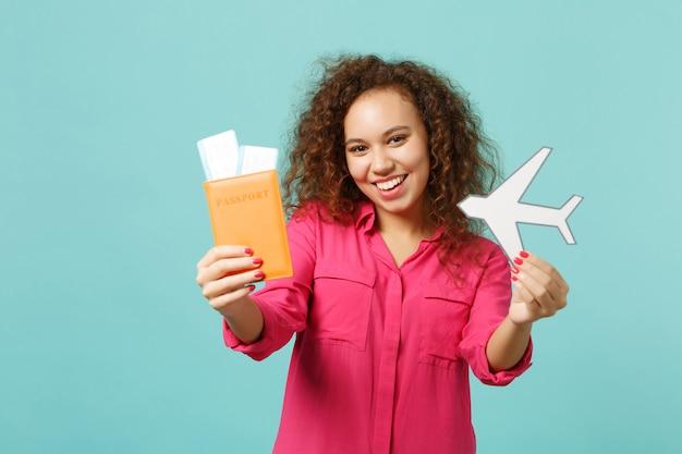 여권, 탑승권, 파란색 청록색 벽 배경에 격리된 종이 비행기를 들고 평상복을 입은 예쁜 아프리카 소녀. 사람들은 진심 어린 감정 라이프 스타일 개념입니다. 복사 공간을 비웃습니다.