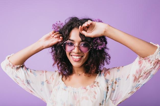 Довольно африканская девушка в хорошем настроении позирует с луком. крытый выстрел привлекательной черной женской модели, танцующей с улыбкой.
