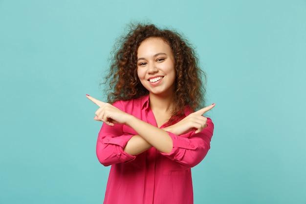 분홍색 캐주얼 옷을 입은 예쁜 아프리카 소녀가 파란색 청록색 벽 배경에 격리된 검지 손가락을 옆으로 가로질러 교차했습니다. 사람들은 진심 어린 감정 라이프 스타일 개념입니다. 복사 공간을 비웃습니다.