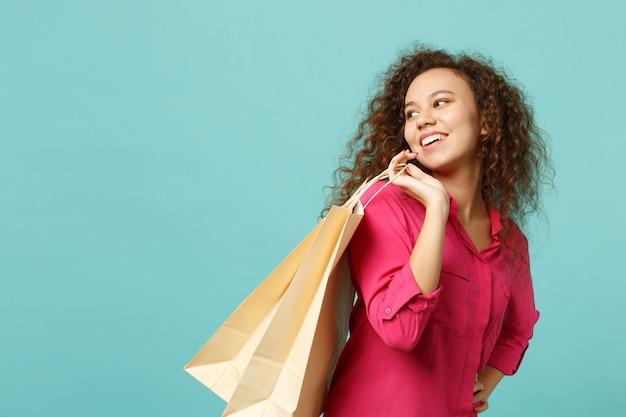 파란색 청록색 벽 배경에서 격리된 쇼핑 후 구매한 패키지 가방을 들고 분홍색 캐주얼 옷을 입은 예쁜 아프리카 소녀. 사람들은 진심 어린 감정 라이프 스타일 개념입니다. 복사 공간을 비웃습니다.