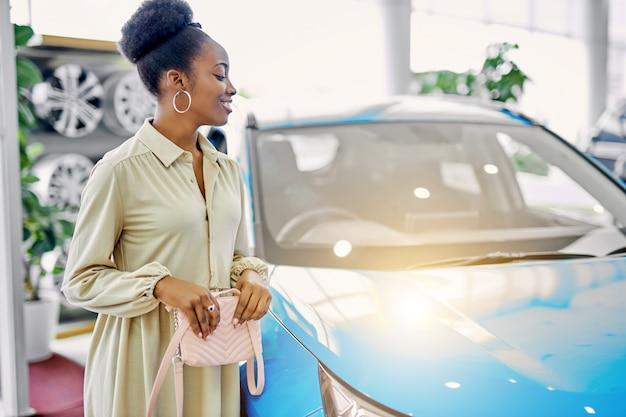 Довольно африканской леди понравился автомобиль в автосалоне