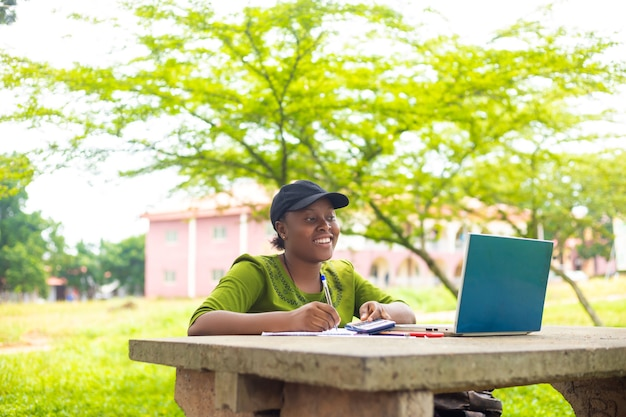 Pretty african student feeling excited as she is working her assignment in the campus