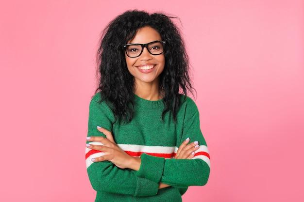 白と赤のストライプと黒のフレームのメガネの緑のスウェットシャツでかわいいアフリカの学生の女の子が腕を組んでポーズをとっています