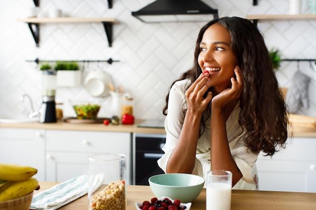 Pretty african woman eats a raspberry before a breakfast