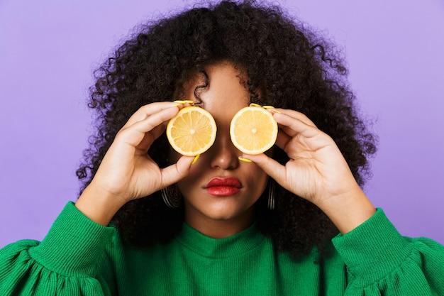 目を覆っているレモンを保持している紫色の空間に孤立したかなりアフリカの女性。