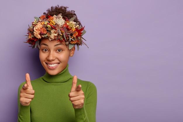 예쁜 아프리카 계 미국인 소녀가 카메라를 직접 가리키고, 손가락 총 제스처를 만들고, 긍정적으로 미소를 짓고, 자신의 선택을 표현하고, 자연 가을 식물 화환을 착용하고, 캐주얼 점퍼를 입고, 실내 포즈를 취합니다.
