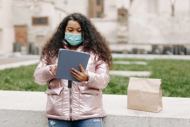 通りに立ってデジタルタブレットを使用している医療マスクのかなりアフロアメリカ人女性。現代のガジェットで屋外で余暇を過ごす若い女性。