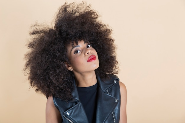 Pretty afro american woman in a leather vest beige background