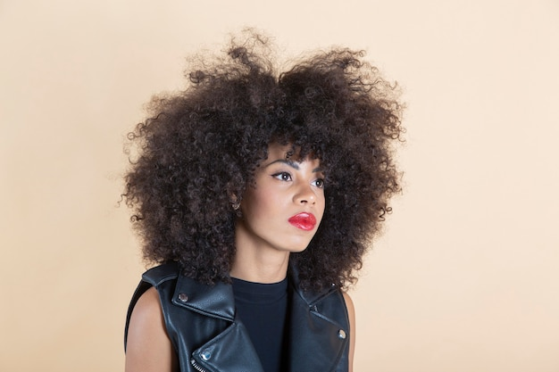 Pretty afro american woman smiling with leather clothes beige background