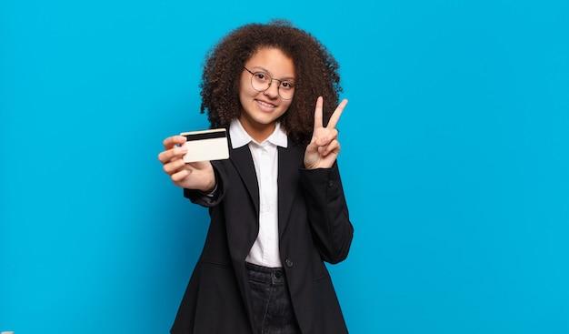 クレジットカードを持つかなりアフロティーンエイジャーのビジネスガール。オンラインショッピングのコンセプト