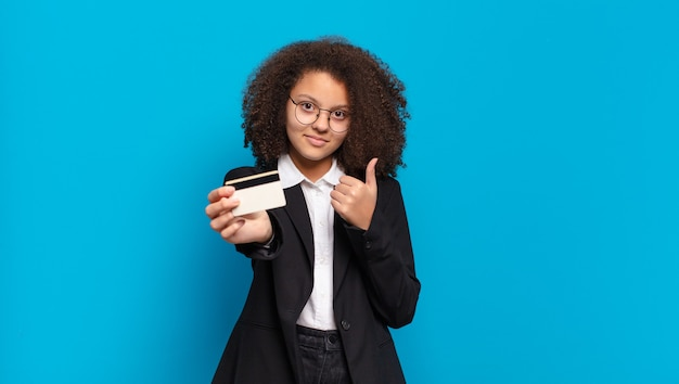 Pretty afro teenager business girl with a credit card. online shopping concept