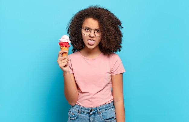 Симпатичный афро-подросток чувствует отвращение и раздражение, высовывает язык, не любит что-то мерзкое и противное. концепция шумерского мороженого