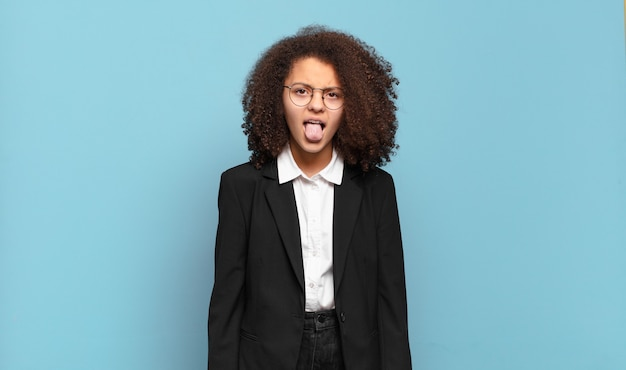 Pretty afro teenager feeling disgusted and irritated, sticking tongue out, disliking something nasty and yucky. humorous business concept