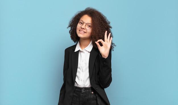 Довольно афро-подросток чувствует себя счастливым, расслабленным и довольным, демонстрирует одобрение с нормальным жестом и улыбается. юмористическая бизнес-концепция