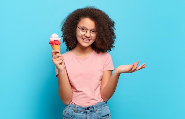 Довольно афро-подросток чувствует себя счастливым, удивленным и веселым, улыбается с позитивным настроем, реализует решение или идею. концепция шумерского мороженого