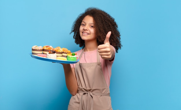 Pretty afro teenager feeling proud, carefree, confident and happy, smiling positively with thumbs up. humorous baker concept