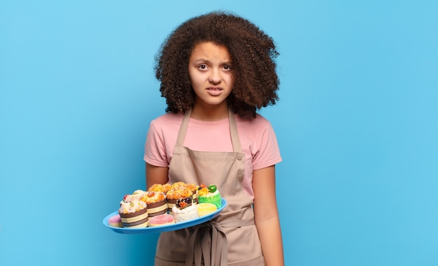 Pretty afro teenager feeling puzzled and confused, with a dumb, stunned expression looking at something unexpected. humorous baker concept