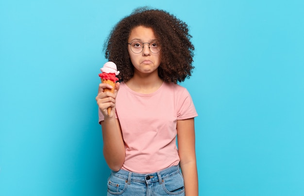 かなりアフロのティーンエイジャーは、不幸な表情で悲しみと泣き言を感じ、否定的で欲求不満の態度で泣いています。シュメールアイスクリームのコンセプト